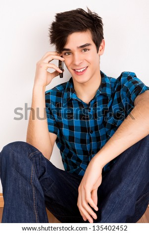 Young man talking on the phone at home - stock photo