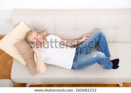 Young man talking on the phone at home on the couch