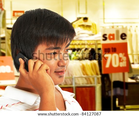 Young Man Talking On The Phone In Front Of A Store Which Has A Sale - stock photo