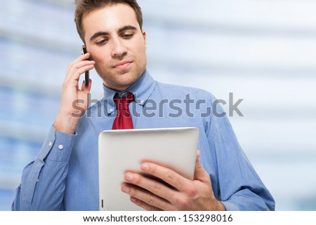 Young man talking on the phone while using his tablet - stock photo