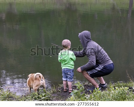 Young man teaching son to fish - stock photo