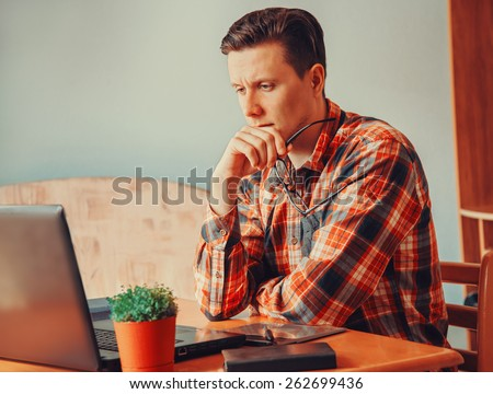 Young man thinking and looking on laptop in the office - stock photo