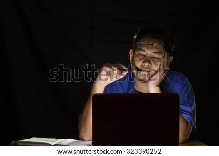 Young man thinking hard in front of his laptop in the dark - stock photo