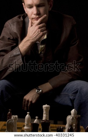 Young man thinking of his next chess move - stock photo