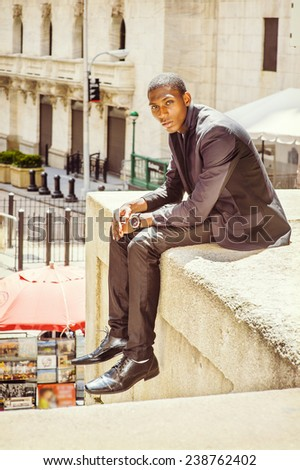 Young man thinking on street. A young black college student is sitting outside, arched the back, holding hands on the laptop, under strong sunshine, relaxing. - stock photo