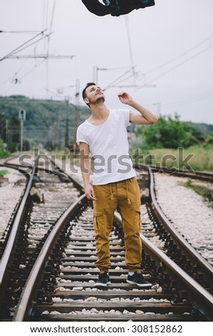 Young man throwing a jacket on the railroad. Vintage Instagram style effect, soft and selective focus, strong clarity, grain texture visible on maximum size - stock photo
