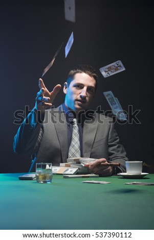 Young man throwing cards, poker