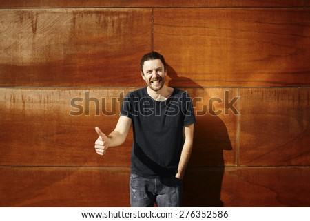 Young man thumbs up. Smiling happy hipster man giving thumbs up success sign to camera during city walk outside at the orange wall. Handsome male model in his 20s.  - stock photo