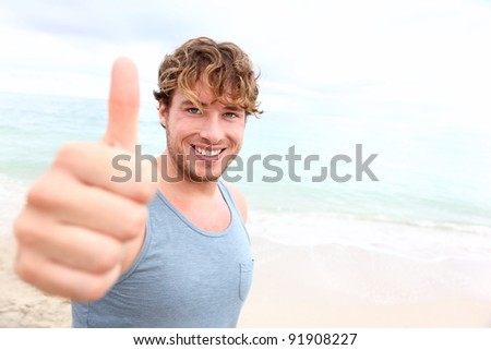 Young man thumbs up. Smiling happy sporty man giving thumbs up success sign to camera during training outside on beach. Handsome male fitness model in his 20s. - stock photo