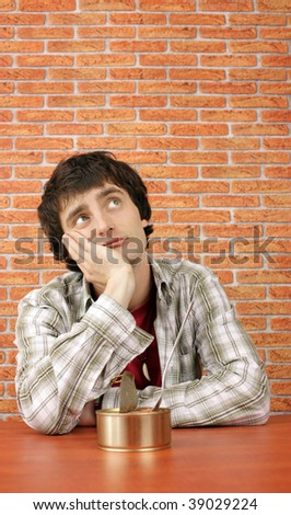 Young man tired of eating canned food - stock photo