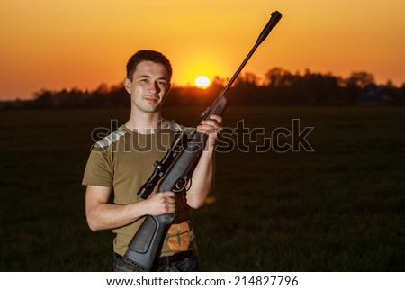 young man took aim with your sniper rifle about rural roads. - stock photo