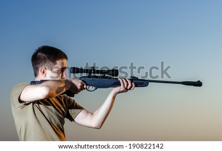 young man took aim with your sniper rifle at sunset.