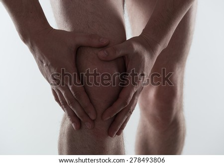 Young man touching his injured knee. Arthritis and joint illness.  - stock photo