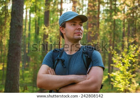 Young man tourist in cap and t-shirt portrait on forest background. - stock photo
