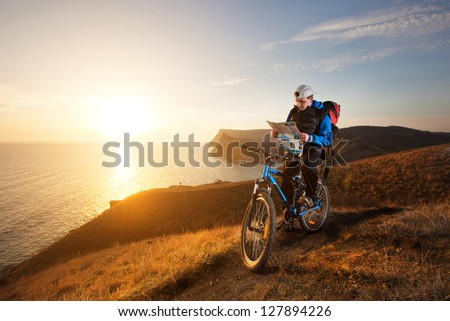 young man tourist on a bicycle traveling at night in the mountains - stock photo