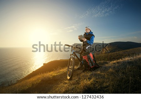 Young man tourist on a cycling. Cyclist tourist studying a map on the tablet at sunset. - stock photo