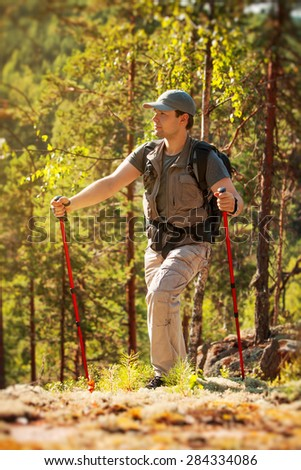 Young man tourist walking on stones in forest in Finland - stock photo