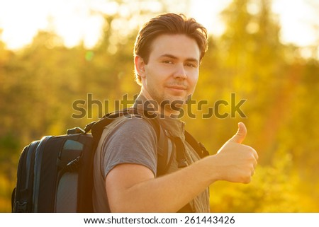 Young man tourist with backpack showing thumbs up handsign. Red sunset light. - stock photo