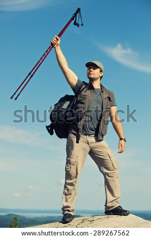Young man tourist with backpack standing on mountain top and holding sticks above head. - stock photo