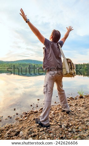Young man tourist with bag standing on lake shore. Wide angle view. - stock photo