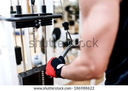 Young man training at gym with triceps exercises. Fitness concept, man working out - stock photo
