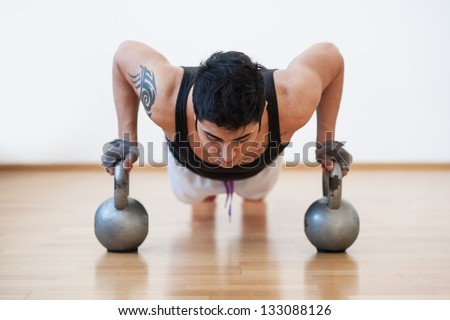 Young man training in the gym with heavy balls.