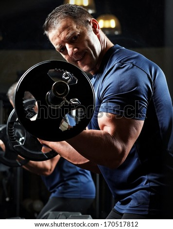 Young man training in the gym with heavy balls.Low light. - stock photo