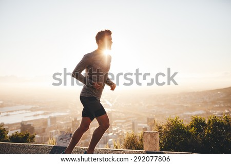 Young man training in the nature with sun behind him. Young man on morning run outdoors. - stock photo