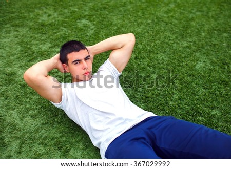 Young man training outdoors and doing sit-ups on green grass.  - stock photo
