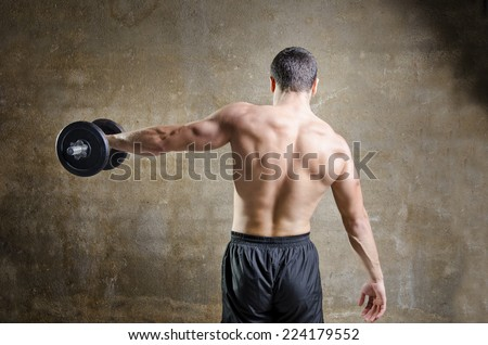 Young man  training shoulder and back muscles exercises in old gym - stock photo