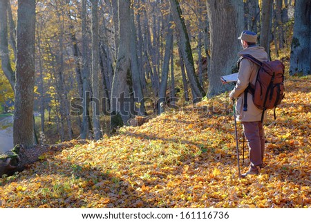 Young man traveler exploring the map in autumn forest.