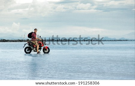Young man traveling on motorcycle over the world standing on the sea behind blue water and sky and mountains feeling freedom on abandoned island with backpack