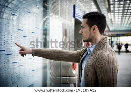 Young man travelling, pointing finger on train timetable in railway station