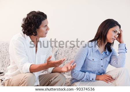 Young man trying to apologize to his girlfriend - stock photo