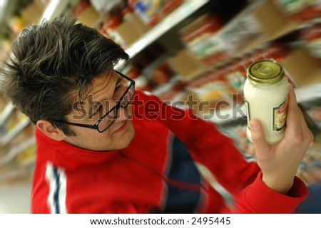 Young man trying to read a label at the supermarket. - stock photo