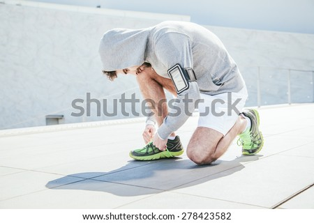 Young man tying his shoe lace in middle of rushing - stock photo