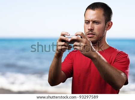 young man typing on a mobile phone against a beach background - stock photo