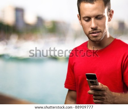 young man typing on mobile phone against a beach background