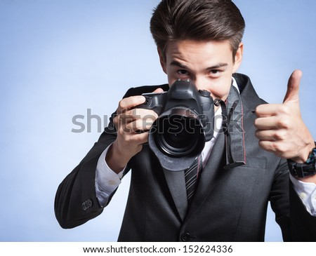 Young man using a professional camera - stock photo