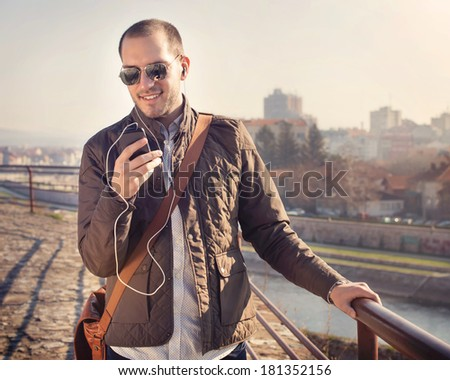 Young man using a smart phone outdoors / white balance correction in photo shop, focal point is on the young man's face. - stock photo