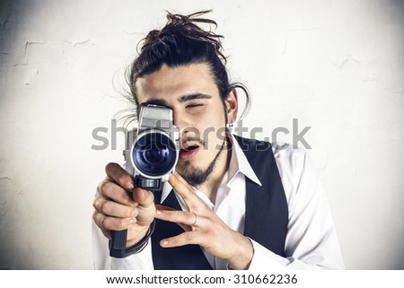 Young man using a vintage camera - stock photo