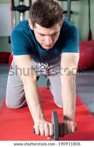Young man using abdominal roller on gym mat - stock photo