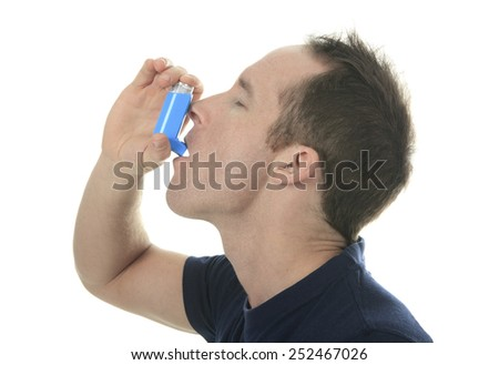 Young man using  an asthma inhaler as prevention - stock photo