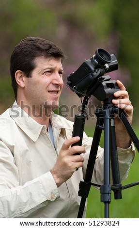 Young man using camcorder on a tripod outdoors in a forest