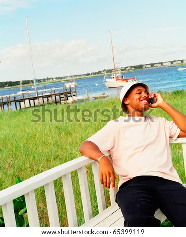 Young man using cell phone at waterfront - stock photo