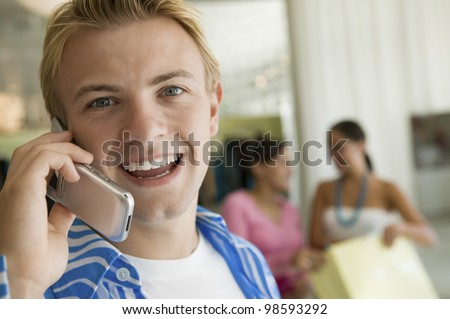 Young Man Using Cell Phone in Store