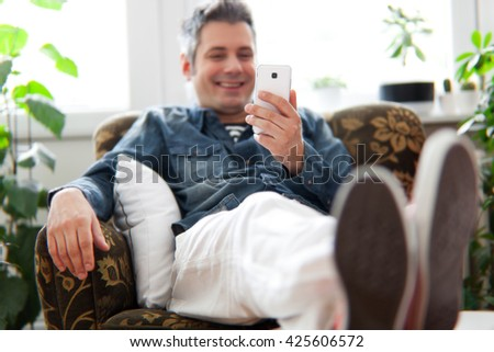 Young man using cell phone while sitting in the armchair, shallow depth of field