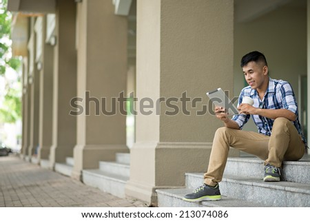 Young man using digital tablet while sitting on the steps - stock photo