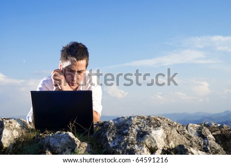 Young man using his laptop, sitting on the  rocky