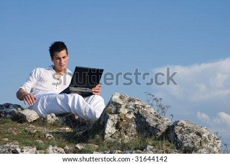 Young man using his laptop sitting on top of the mountain